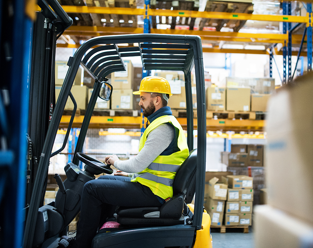 Man driving electric forklift from a side view profile