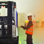 Engineer inspecting a forklift truck holding a clipboard