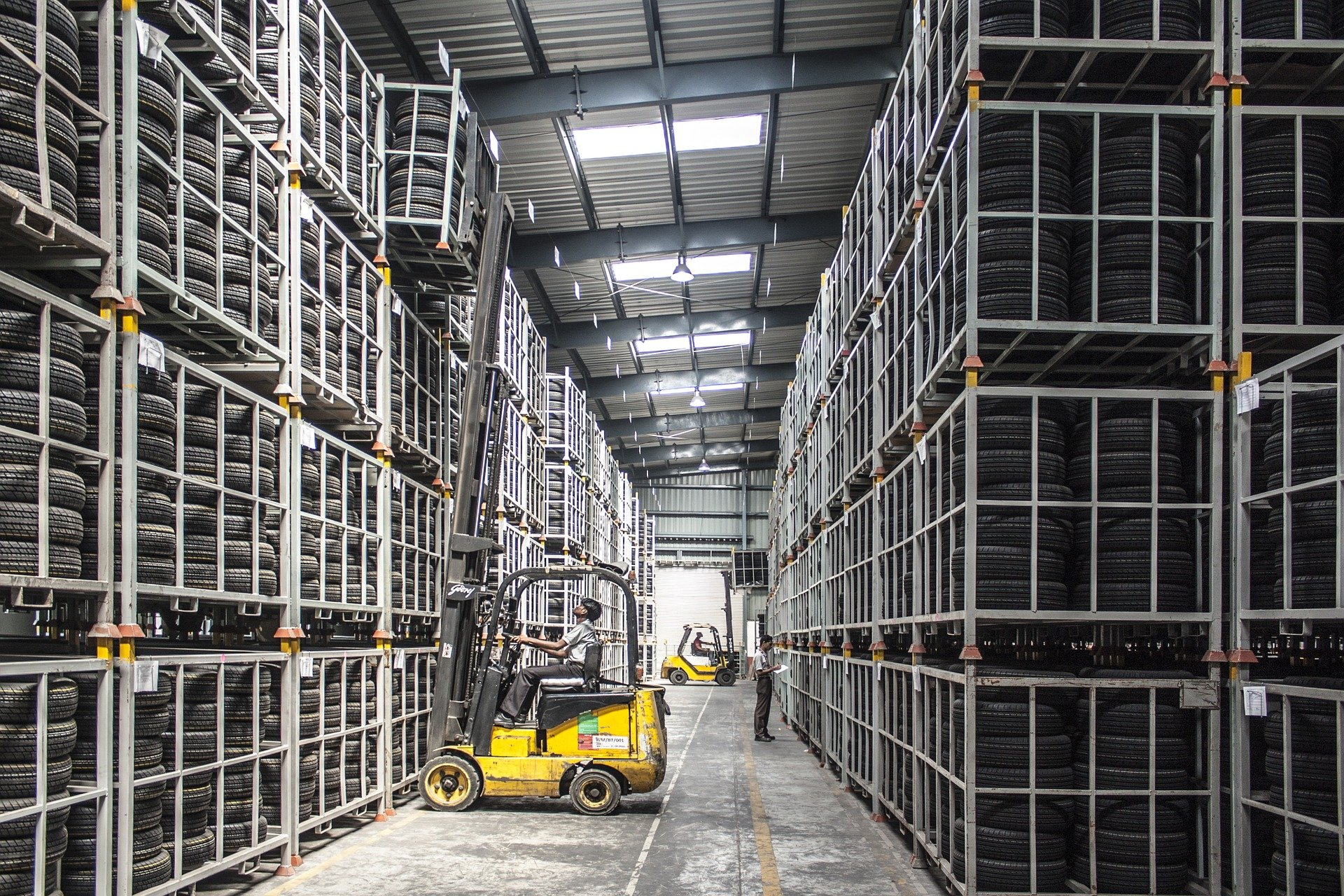 Forklift truck lifting a cage at full reach